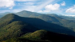 A view from The Long Trail at Mount Mansfield shows rolling green mountains in Vermont