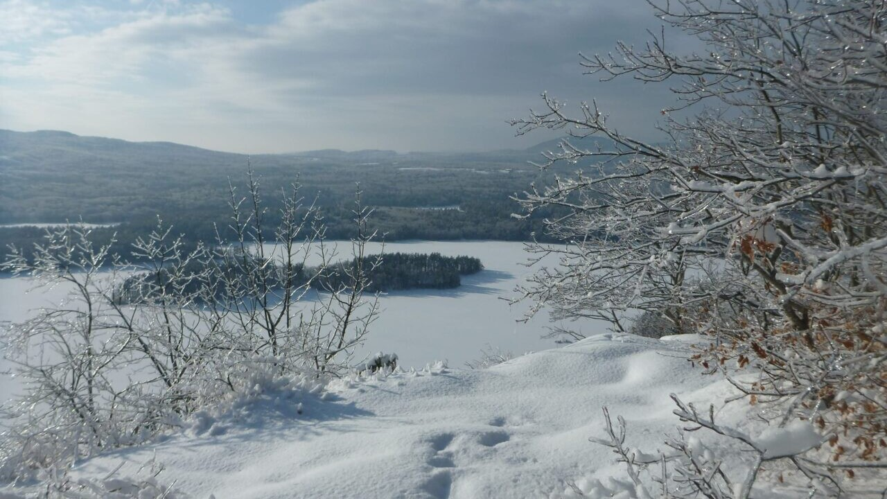 A beautiful view overlooks a snowy landscape and a frozen lake.