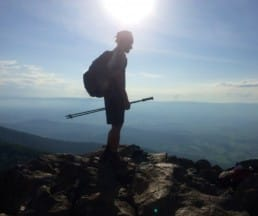 A hiker stands on a rocky peak overlooking a valley.