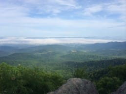 A view shows clouds sitting in a distant green valley.
