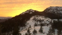 A brilliant yellow and orange sunset appears from behind a snowy mountain.