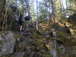 Two hikers climb a mossy, rocky outcropping.