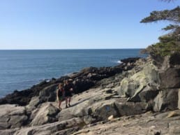 Two hikers stand on massive boulders on Maine's rocky coast.