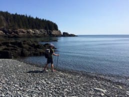 A hiker stands on a rocky beach looking out at blue water and blue sky.
