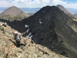 A hiker points at a distant view while climbing a rocky ridgeline.