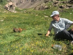 A hiker and a small animal sit in a grassy field.