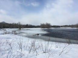 A river winds through a frozen, snowy landscape.