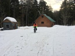 A person rides a bike through snow in front of two small buildings.