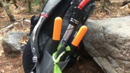 A hiking backpack with many tools for trail maintenance sits on the ground next to a rock.