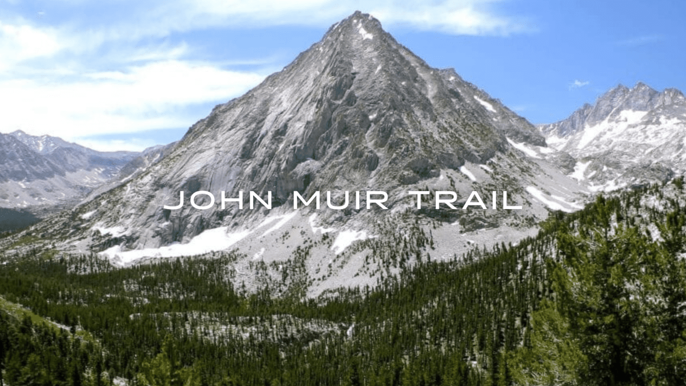 The John Muir Trail offers a commanding view of a rocky mountain peak with patchy snow surrounded by an evergreen forest.