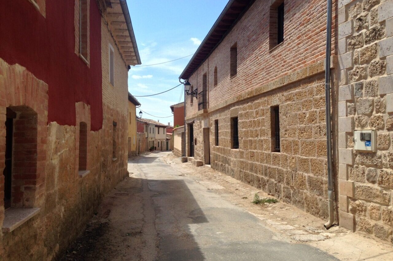 A country road winds through a town of stone buildings.