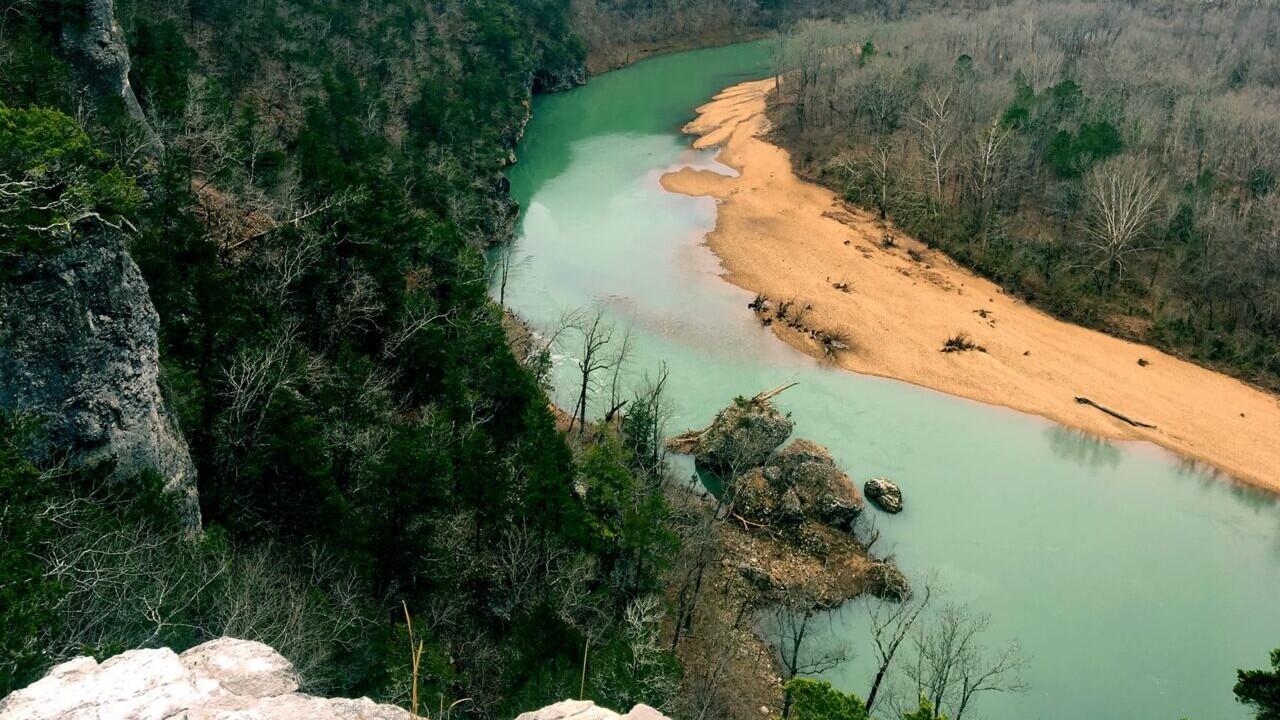 On the Ozark Highlands Trail in Arkansas a view looks over a teal river with a sandy beach and dense forests.
