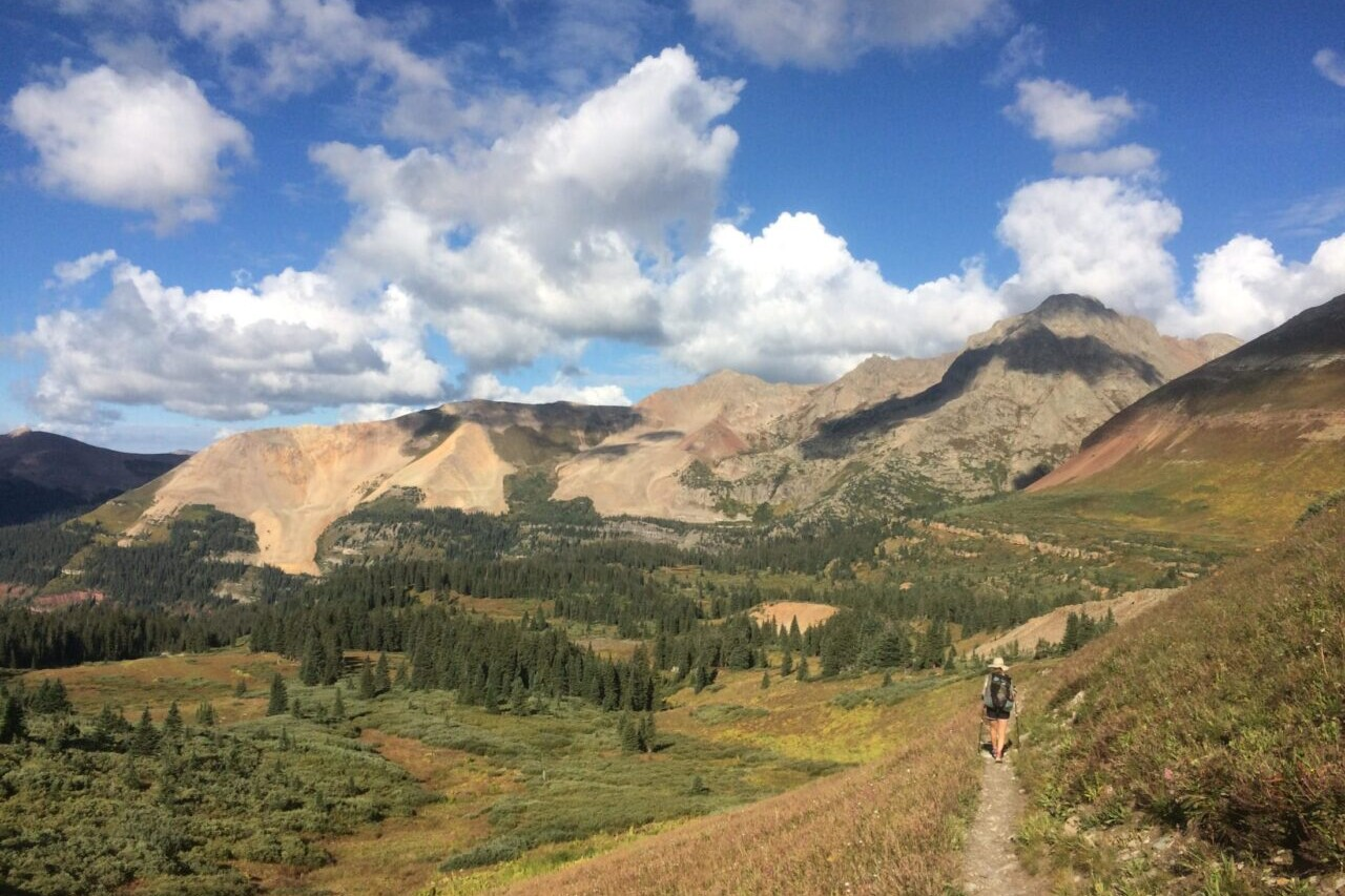 A trail winds around a golden hillside with rocky mountains in the distance.