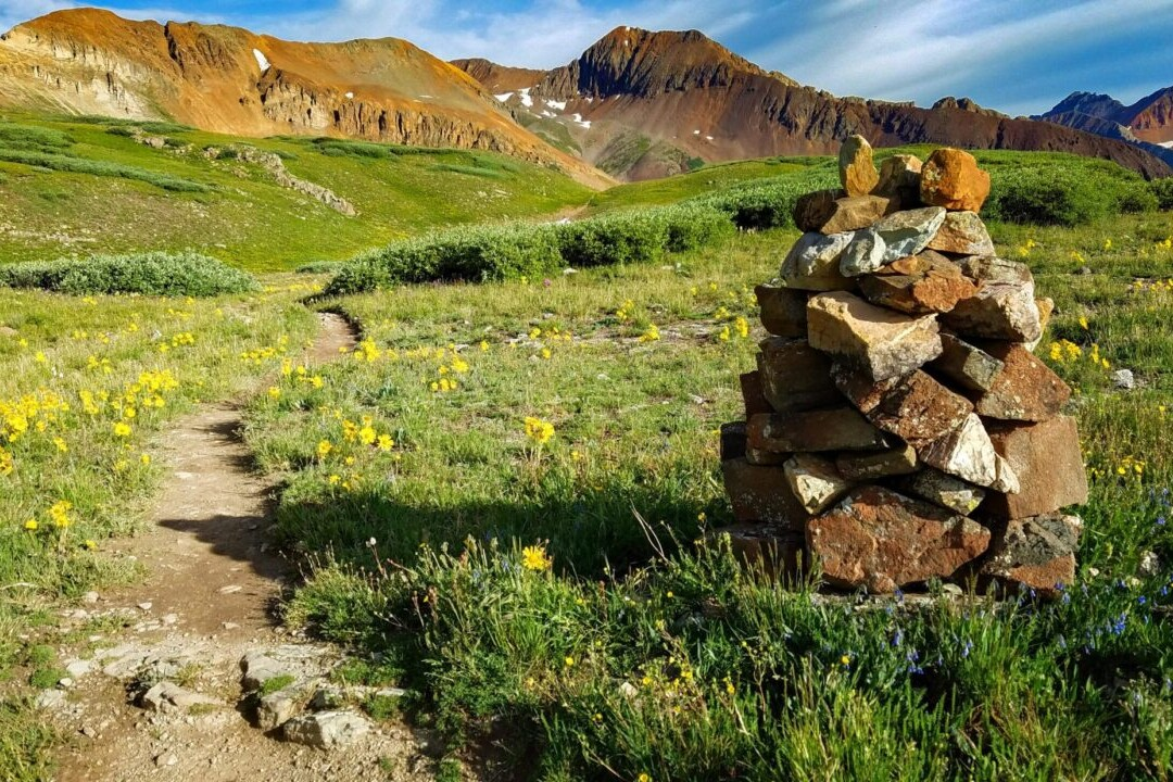 A trail winds through a green meadow past a rock cairn with rocky mountains in the distance.