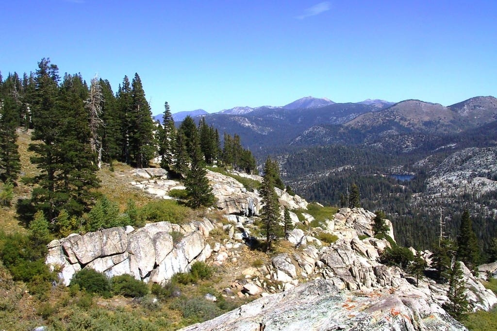 A rocky ridge and meadows overlook distant rocky mountains.