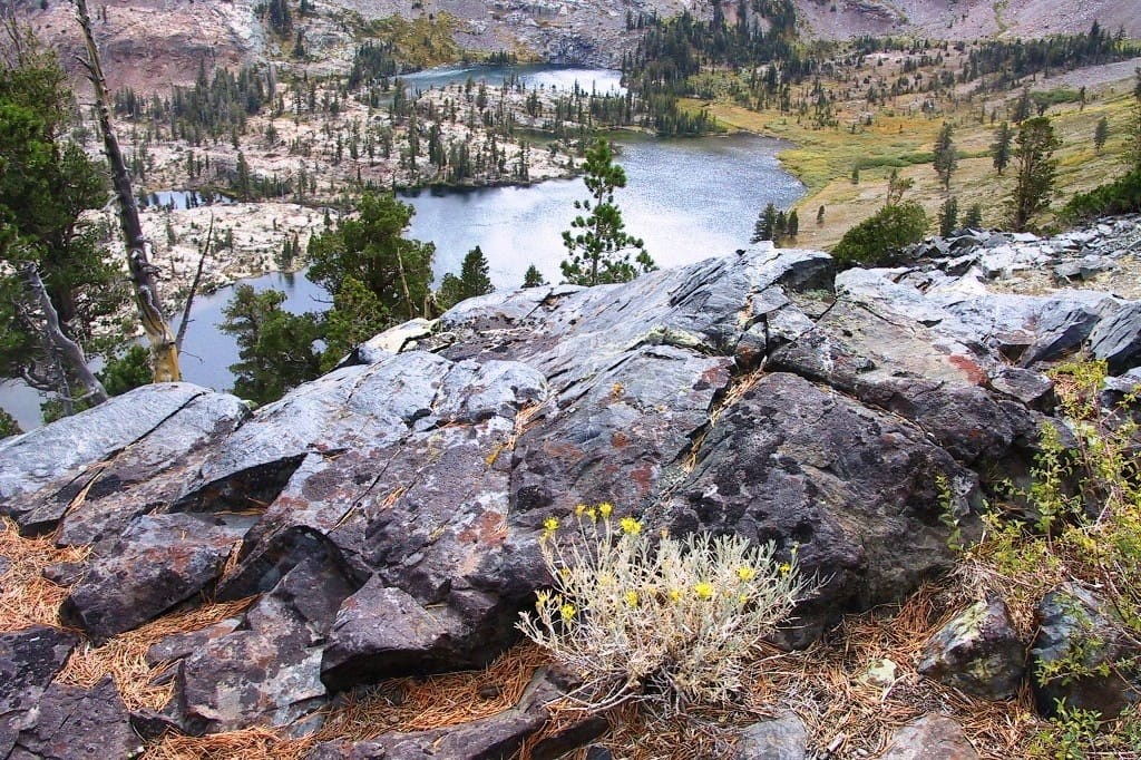 A rocky view overlooks a blue lake and meadows.