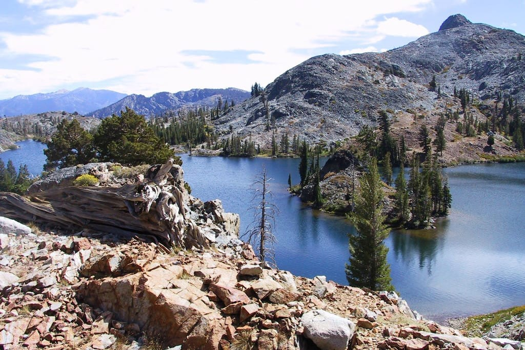 A rocky view overlooks a blue lake and mountains.
