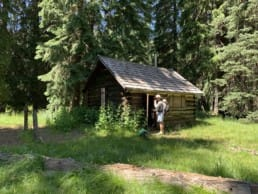 A hiker and a dog stand in front of a cabin in a meadow with an evergreen forest in the background.