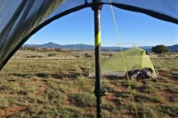 The view from inside a tent shows another tent in an open field and distant mountains.