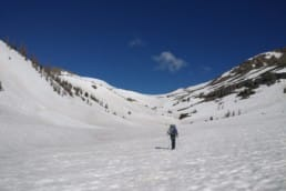 A hiker crosses a snowfield towards a pass.