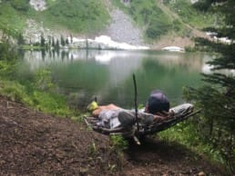 A hiker lounges by a green lake.