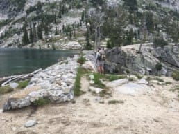 A hiker and a dog stand near a manmade dam and an alpine lake.