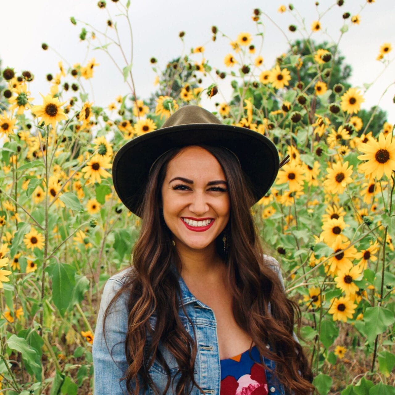 A woman wearing a denim jacket and a brown hat stands in a field of wildflowers.