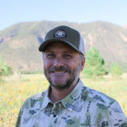 A man wearing an Arizona Trail baseball cap stands in a field in front of a mountain.