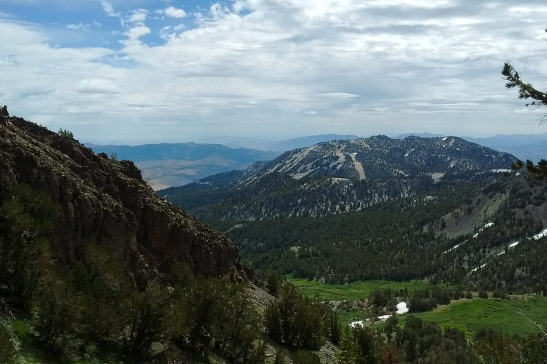 A view overlooks meadows and distant mountains.