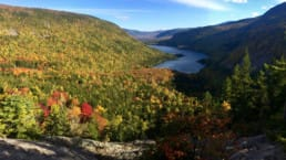 A view from a mountain ridge overlooks orange, red, yellow, and green trees and a blue lake in Baxter State Park in Maine.