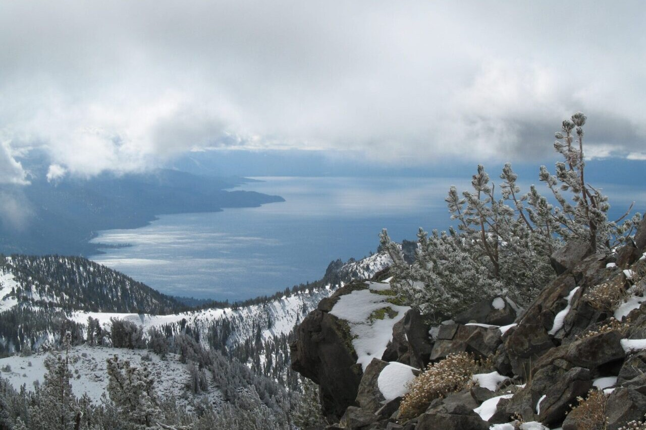 A rocky view overlooks a blue lake and meadows under a cloudy sky.