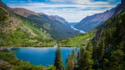 Glenn's Lake sits in a beautiful green valley between majestic peaks in Glacier National Park on the Pacific Northwest Trail.