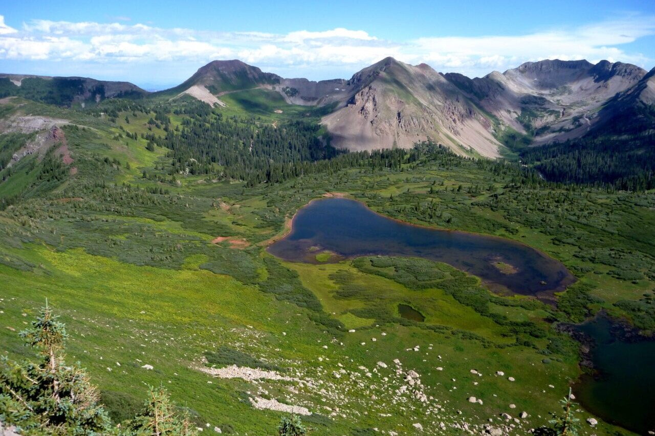A view looks over a blue lake in a green valley surrounded by rocky mountains.