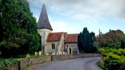 A paved road leads to an old stone church on England's South Downs Way.