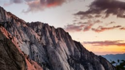 A sunrise glows behind a pale rocky ridge on the Mount Whitney Trail.