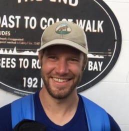 A man wears a blue shirt, blue backpack, and a tan baseball cap.