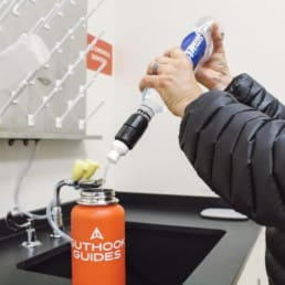 Close up of man holding Smartwater bottle attached to Micro Queeze filter, filtering water into a water bottle.