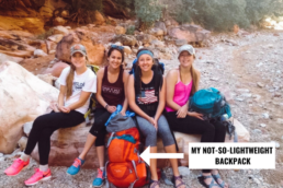 Girls hiking to Havasu Falls and resting on a rock with their backpacking backpacks.