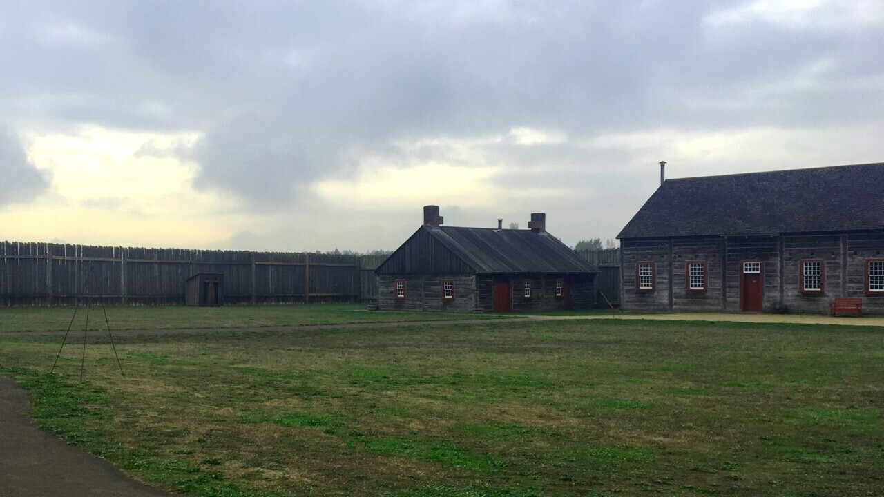Two wooden buildings sit on a green field within a wooden wall at Fort vancouver National Historic Site.