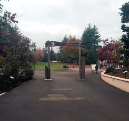 A wooden archway with Native American art sits in the middle of a sidewalk.