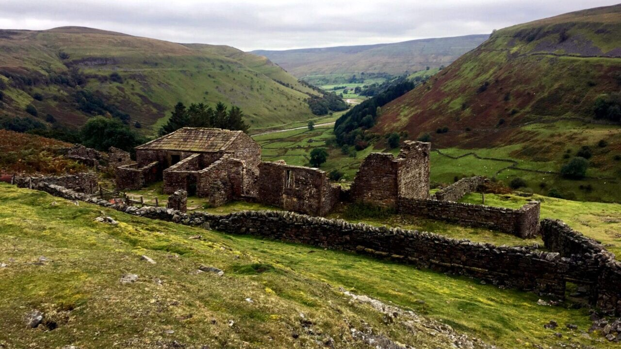 A stone ruin sits in a green field in front of rolling hills.