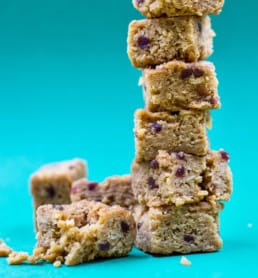 Granola bars are stacked up against a blue background.