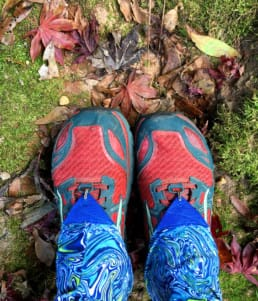 A hiker wears gaiters and trail running shoes while hiking.