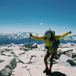 A thru hiker stands on top of a mountain with her arms up.