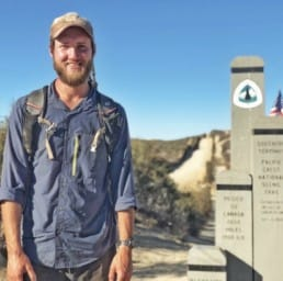 A thru hiker poses by the southern PCT terminus.