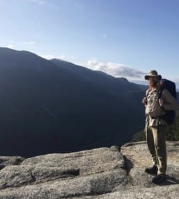A thru hiker standing with a mountain in the background.