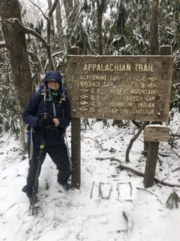A hiker next to an Appalachian Trail sign in the snow.