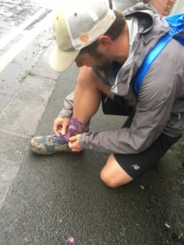 A hiker getting his shoes ready for a day on the trail