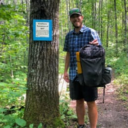 A man with a backpack standing next to a tree on a trail.