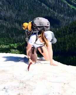 A woman with a backpack climbs up a snowy mountain.